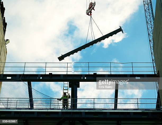 Construction worker positioning a piece of steel.