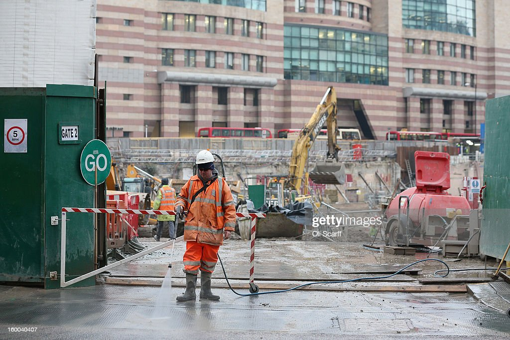 A construction worker pressure-washes the street in front of a building site in the City of London after a lorry has passed on January 25, 2013 in London, England.