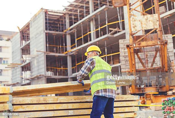 Construction worker putting planks on pile near crane