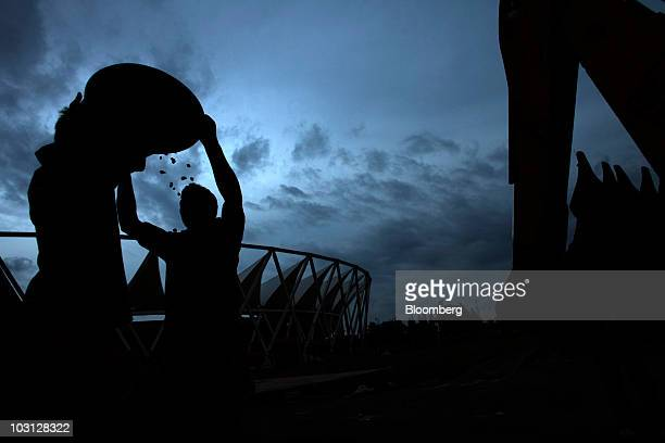 A construction worker raises a bucket of gravel above his head at the Jawaharlal Nehru Stadium in New Delhi India on Tuesday July 27 2010...