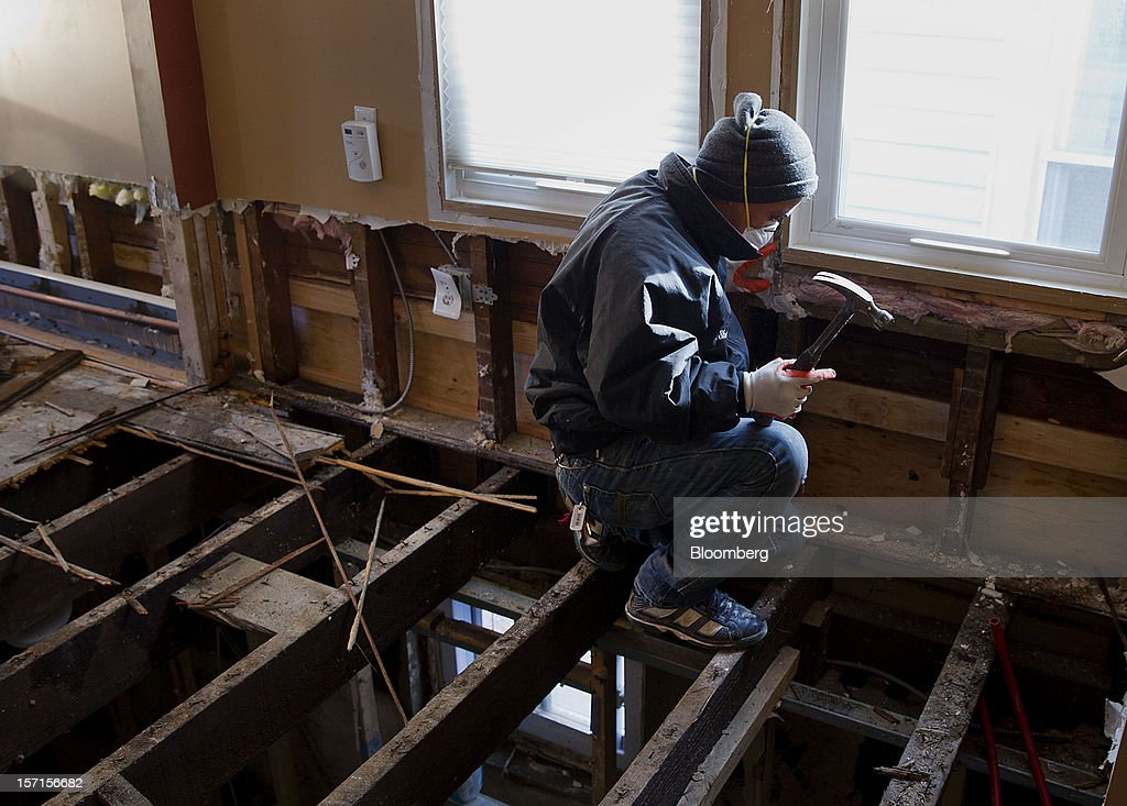 A construction worker repairs a home in the Staten Island borough of New York, U.S., on Wednesday, Nov. 28, 2012. Superstorm Sandy is giving the U.S. Northeast, and the rest of the country, an economic boost that may eventually surpass the loss of business it caused. Photographer: Jin Lee/Bloomberg via Getty Images