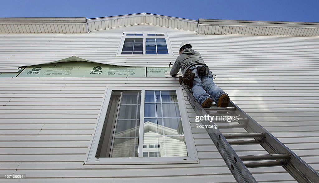 A construction worker repairs siding on a home in the Staten Island borough of New York, U.S., on Wednesday, Nov. 28, 2012. Superstorm Sandy is giving the U.S. Northeast, and the rest of the country, an economic boost that may eventually surpass the loss of business it caused. Photographer: Jin Lee/Bloomberg via Getty Images