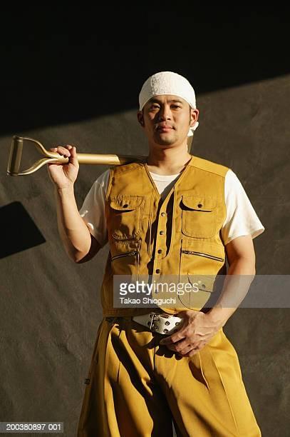 Construction worker resting shovel on shoulder, portrait