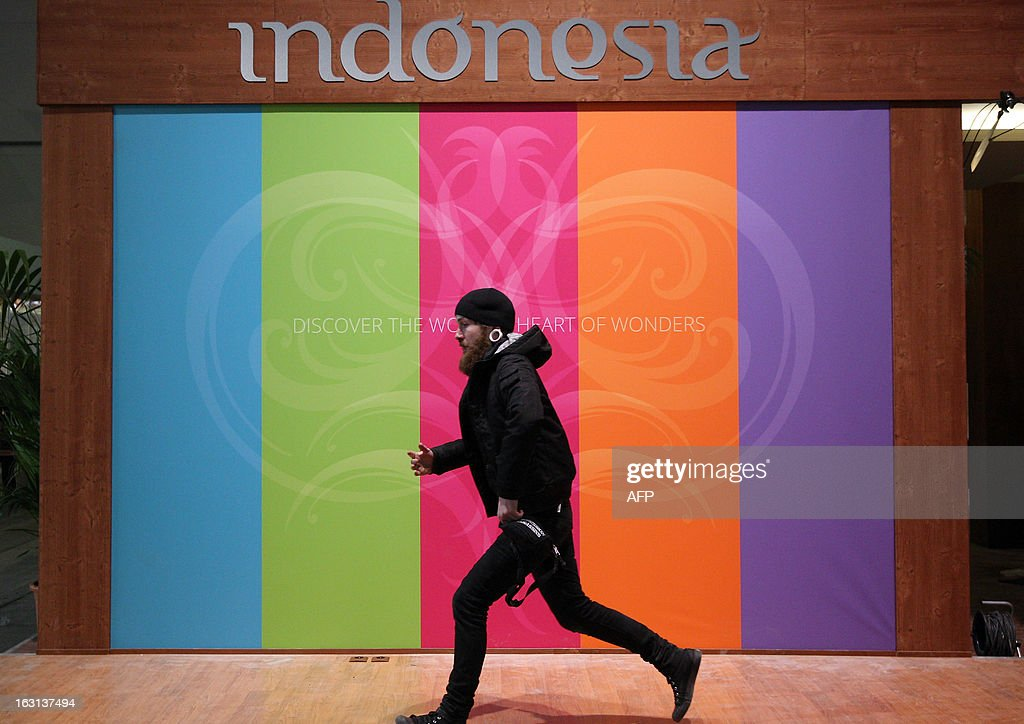 A construction worker runs through the stand for Indonesia at the ITB Berlin tourism convention (Internationale Tourismus-Boerse) prior to its opening in Berlin on March 5, 2013. The ITB Berlin runs from March 6-10 and features Indonesia as its partner country for the event in 2013. AFP PHOTO / ADAM BERRY