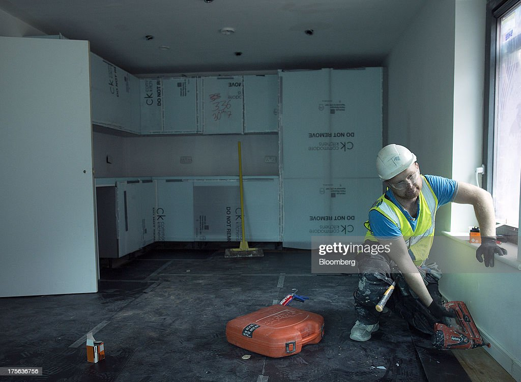 A construction worker secures a skirting board to a wall inside an apartment at the Oval Quarter, a shared ownership, private and social residential housing complex developed by Higgins Group Plc in partnership with Nottinghill Housing and Pinnacle Regeneration Group, in London, U.K., on Monday, Aug. 5, 2013. U.K. house prices rose 0.8 percent in July, from 0.3 percent the previous month, Nationwide Building Society said. Photographer: Simon Dawson/Bloomberg via Getty Images