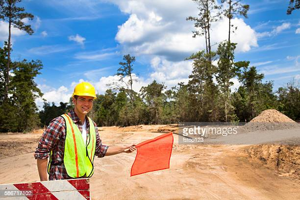 Construction worker, signalman directs traffic at job site.