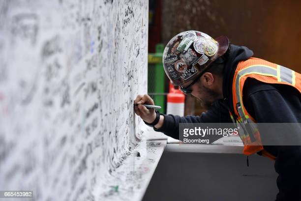 A construction worker signs the final steel beam during a topping off ceremony for the Salesforce Tower in San Francisco California US on Thursday...