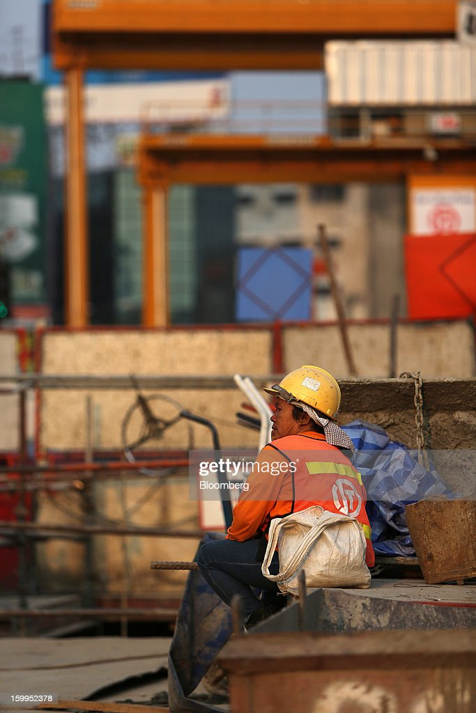 A construction worker sits at a building site in Bangkok, Thailand, on Wednesday, Jan. 23, 2013. Prime Minister Yingluck Shinawatra's government last month approved a new round of increases in the daily minimum wage to 300 baht ($9.8) from the beginning of this year, after a similar raise in April in seven provinces including Bangkok. Photographer: Dario Pignatelli/Bloomberg via Getty Images