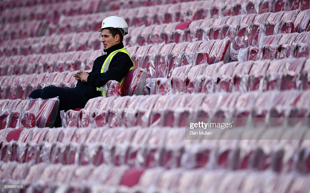 A construction worker sits in an unopened stand during the Sky Bet Championship match between Bristol City and Huddersfield Town at Ashton Gate on April 30, 2016 in Bristol, England.