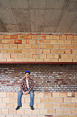 Construction Worker Sitting on a Wall