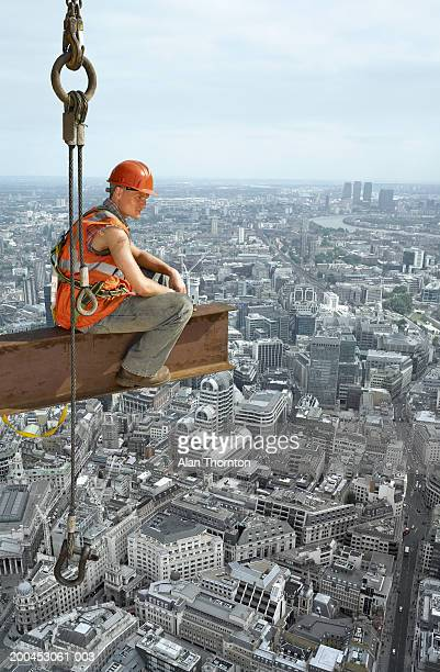 Construction worker sitting on beam above cityscape, digital composite
