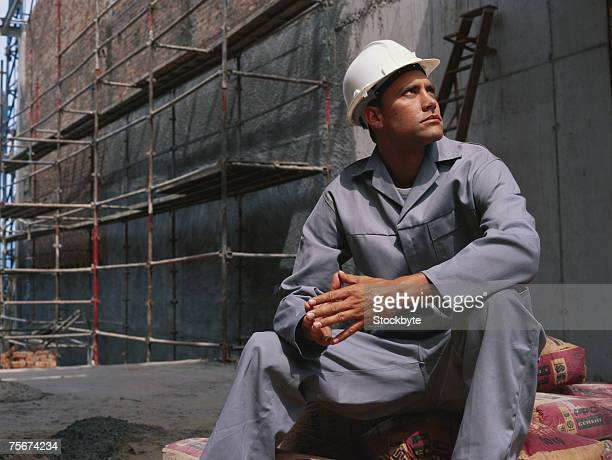 Construction worker sitting on cement sack, looking up