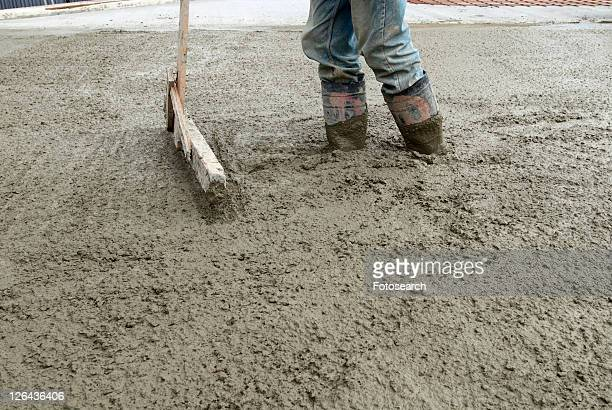 Construction worker smoothing concrete after a pour.