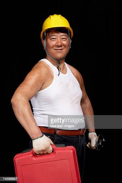 Construction worker standing with wrench and drill box