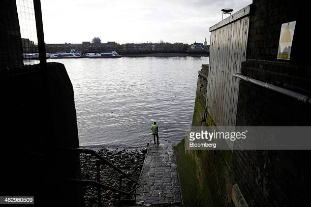 A construction worker stands at the shore of the River Thames looking out towards Greenwich from Wapping High Street in London UK on Thursday Jan 16...