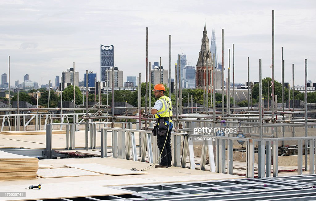 A construction worker stands by scaffolding at the Oval Quarter, a shared ownership, private and social residential housing complex developed by Higgins Group Plc in partnership with Nottinghill Housing and Pinnacle Regeneration Group, in London, U.K., on Monday, Aug. 5, 2013. U.K. house prices rose 0.8 percent in July, from 0.3 percent the previous month, Nationwide Building Society said. Photographer: Simon Dawson/Bloomberg via Getty Images