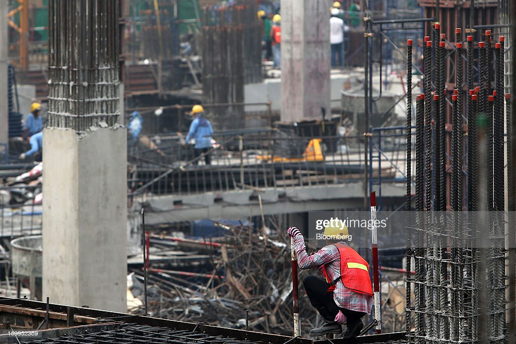 A construction worker stands on a building site at Siam Square in Bangkok, Thailand, on Wednesday, Jan. 23, 2013. Prime Minister Yingluck Shinawatra's government last month approved a new round of increases in the daily minimum wage to 300 baht ($9.8) from the beginning of this year, after a similar raise in April in seven provinces including Bangkok. Photographer: Dario Pignatelli/Bloomberg via Getty Images