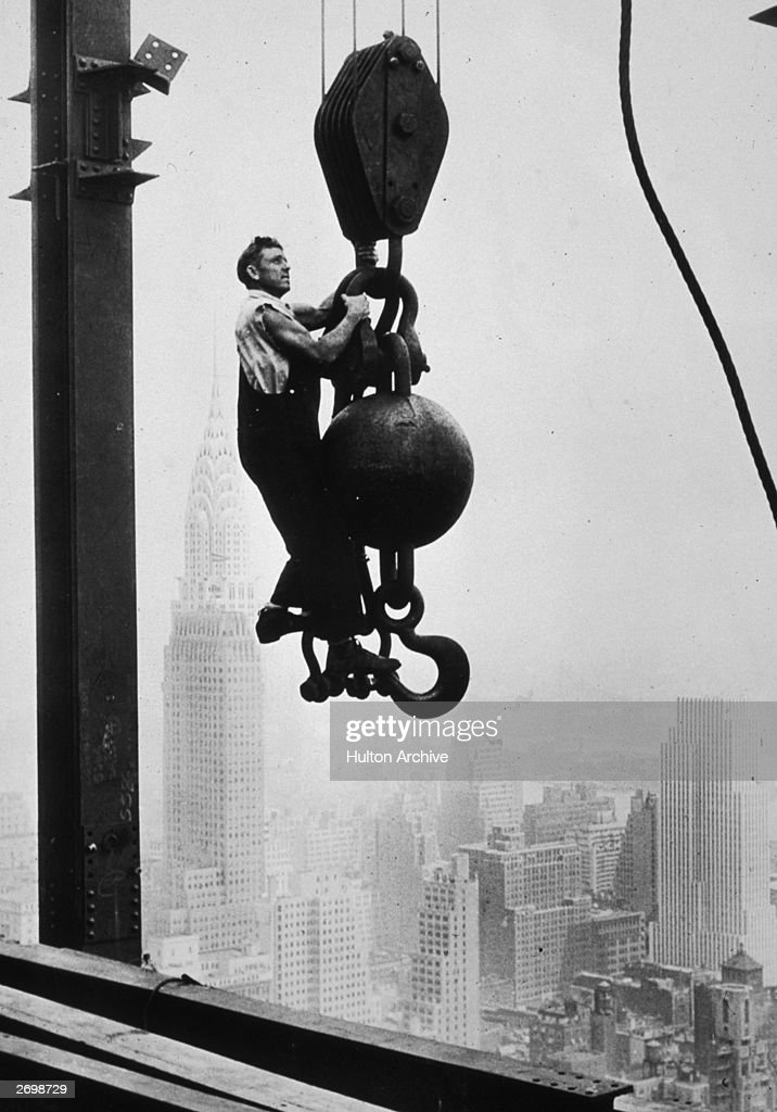 A construction worker hanging on a wrecking ball pulley while working on the Empire State Building in New York. The Chrysler building is behind him.