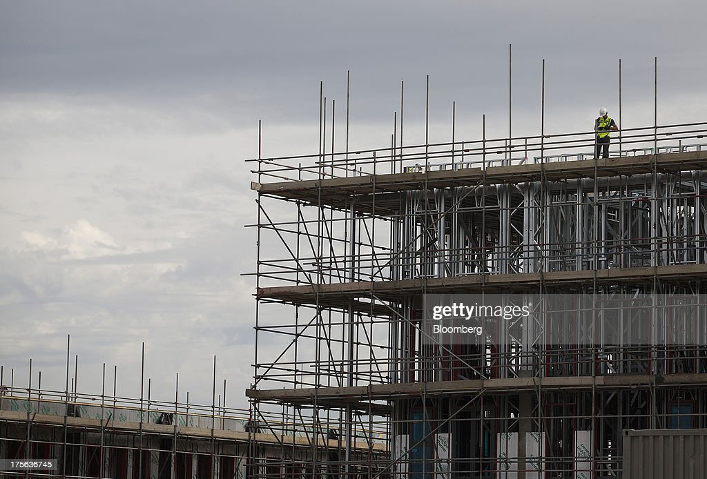 A construction worker stands on scaffolding at the Oval Quarter, a shared ownership, private and social residential housing complex developed by Higgins Group Plc in partnership with Nottinghill Housing and Pinnacle Regeneration Group, in London, U.K., on Monday, Aug. 5, 2013. U.K. house prices rose 0.8 percent in July, from 0.3 percent the previous month, Nationwide Building Society said. Photographer: Simon Dawson/Bloomberg via Getty Images
