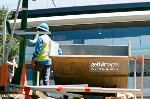 A construction worker stands with a dumpster with windows of the main building visible blocked with white paper and painter's tape at the Apple Park...