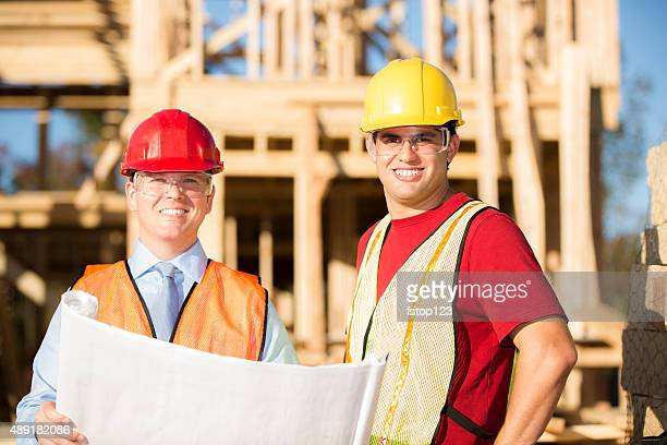 Construction worker, supervisor discuss blueprints at work site. Building.