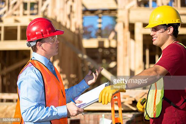 Construction worker, supervisor discuss job at work site. Building.