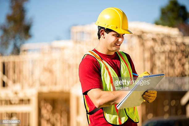 Construction worker, supervisor inspects work at building site. Latin man.