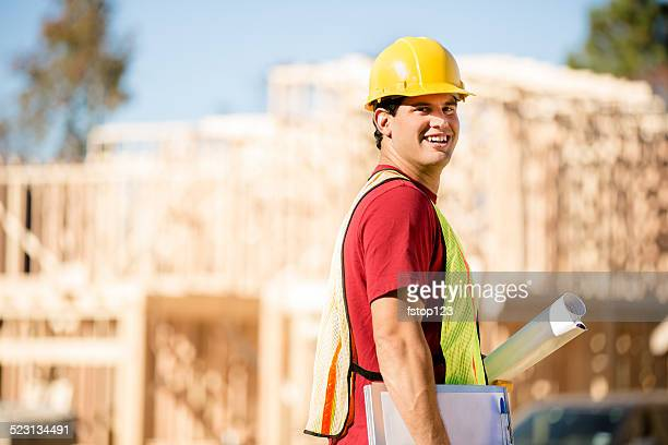 Construction worker, supervisor inspects work at building site.