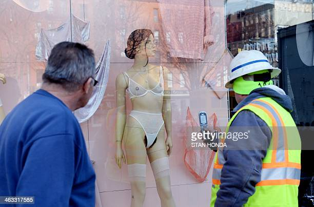 A construction worker takes a cell phone photograph of a mannequin with pubic hair in the window of an American Apparel shop on Houston Street in the...