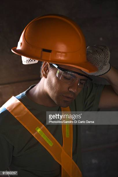 Construction worker taking hard hat off wiping brow with back of hand