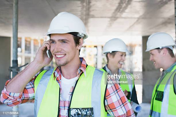 Construction worker talking on cell phone on construction site