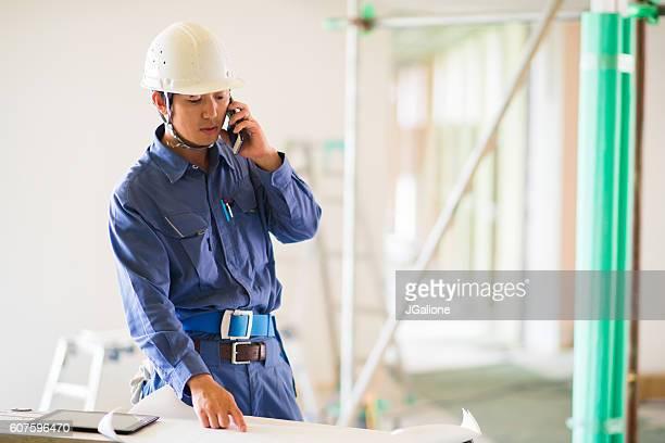 建設作業員、電話で話している