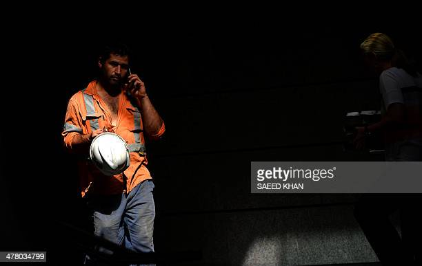 A construction worker talks on his mobile phone during a lunch break in the central business district of Sydney on March 12 2014 The Australian...