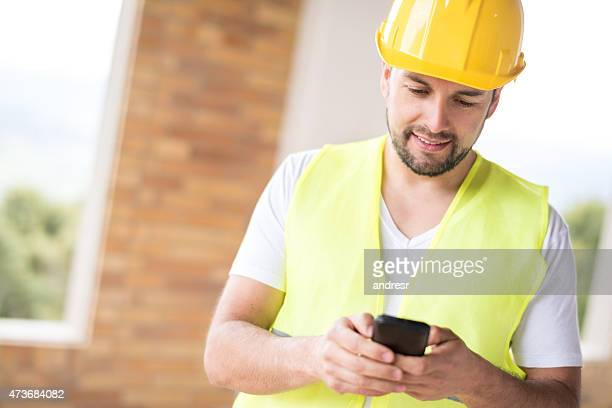 Construction worker texting on a mobile phone