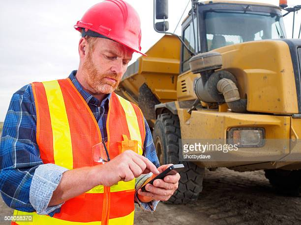 Construction worker, truck, texting and internet and engineer