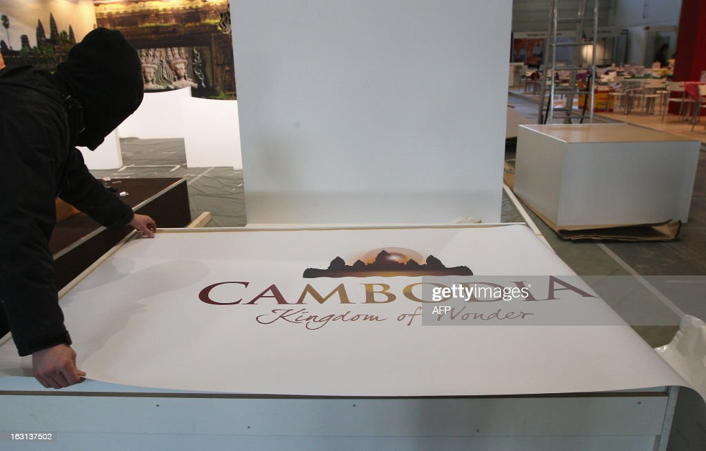 A construction worker unrolls a banner at the stand for Cambodia at the ITB Berlin tourism convention (Internationale Tourismus-Boerse) prior to its opening in Berlin on March 5, 2013. The ITB Berlin runs from March 6-10 and features Indonesia as its partner country for the event in 2013.