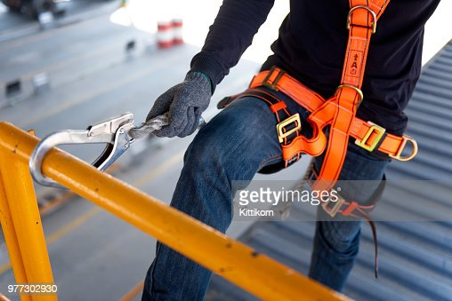 Construction worker use safety harness and safety line working on a new construction site project. : Stock Photo
