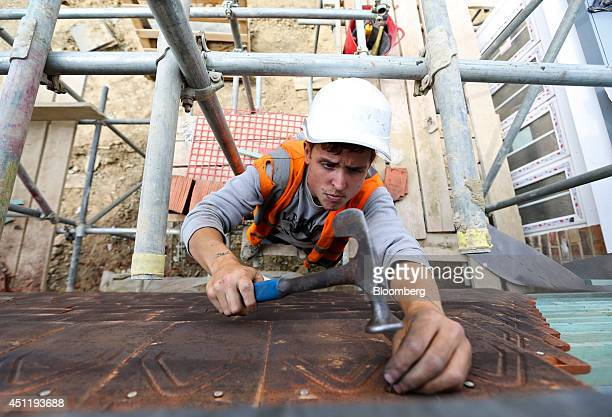 A construction worker uses a hammer to nail tiles to the wall of a new home under construction at a Crest Nicholson Holdings Plc residential housing...