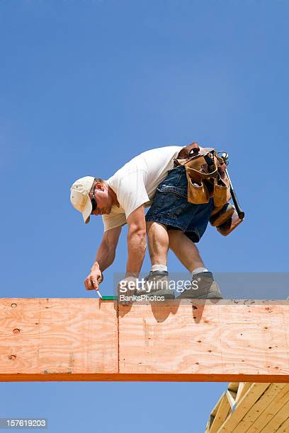 Construction Worker Using a Speed Square on Laminated Lumber Beams