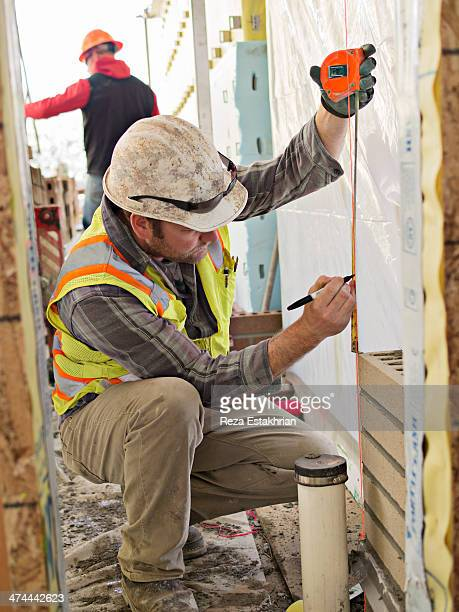 Construction worker using tape measure