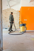 A construction worker vacuums the cement floor with a wet/dry vac.