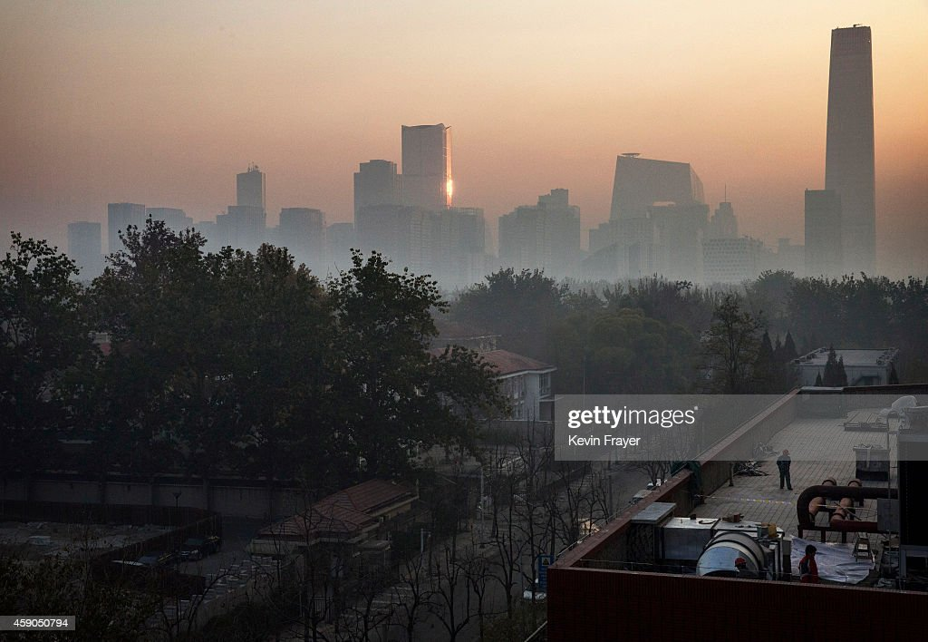 A construction worker walks on a rooftop as smog covers the skyline on November 16 2014 in Beijing China US President Barack Obama and China's...