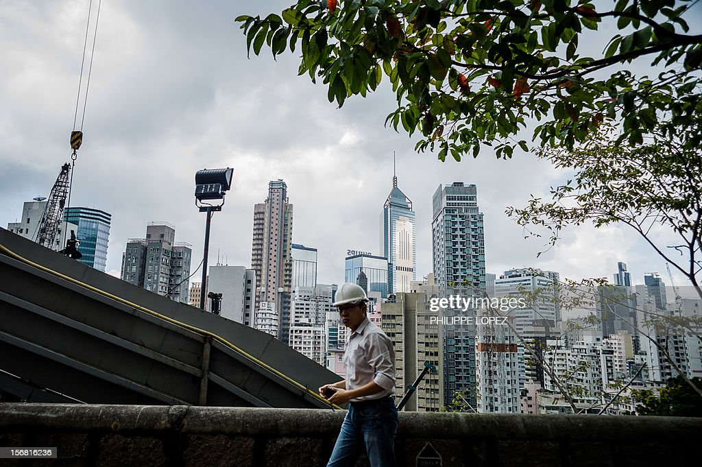 A construction worker walks past the fence of a building site in front of the city's skyline in Hong Kong on November 22, 2012. Hong Kong's economy returned to modest growth in the third quarter, meaning the southern Chinese city avoided a technical recession, typically defined by GDP contractions in two consecutive quarters. AFP PHOTO / Philippe Lopez