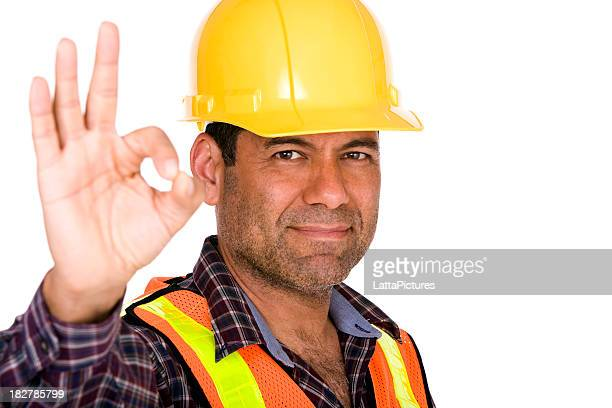 Construction worker wearing hard hat gesturing okay with hand