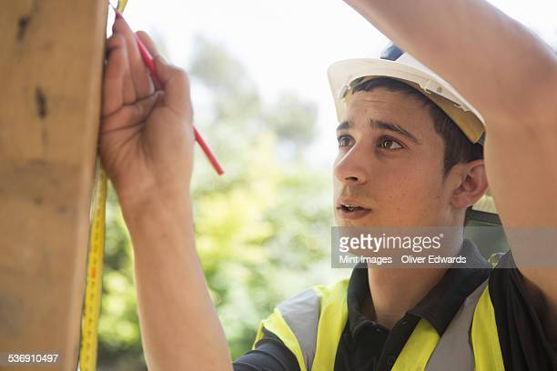 Construction worker wearing high visibility vest and safety helmet.