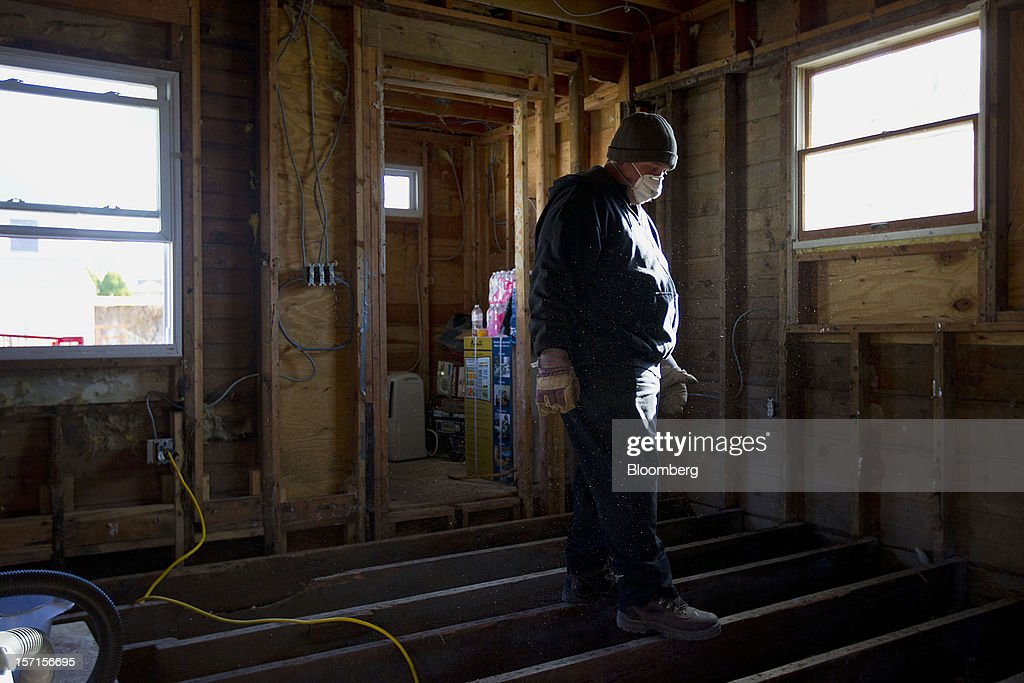 A construction worker wears a mask while standing on the floor boards of a home being repaired in the Staten Island borough of New York, U.S., on Wednesday, Nov. 28, 2012. Superstorm Sandy is giving the U.S. Northeast, and the rest of the country, an economic boost that may eventually surpass the loss of business it caused. Photographer: Jin Lee/Bloomberg via Getty Images