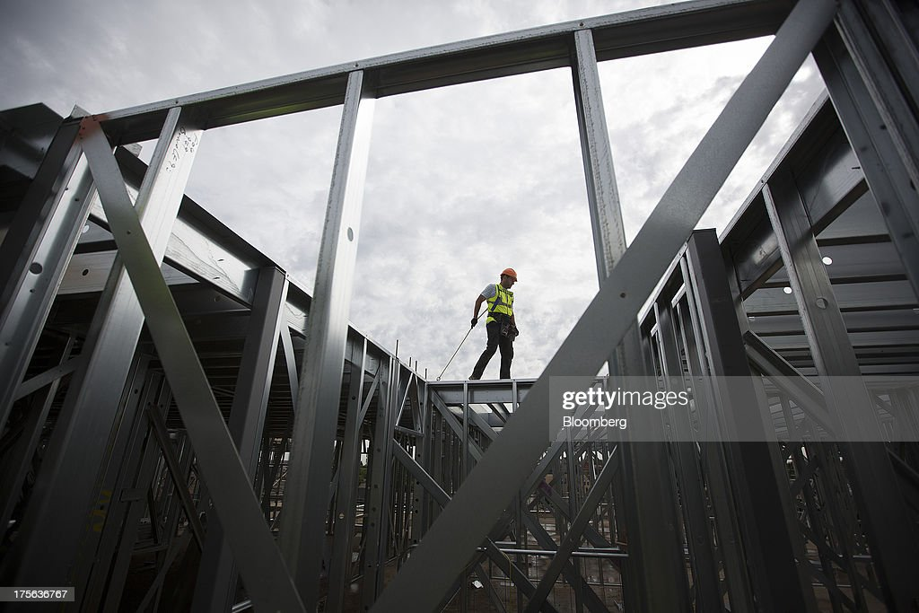 A construction worker wears a tether as he stands on steal beams at the Oval Quarter, a shared ownership, private and social residential housing complex developed by Higgins Group Plc in partnership with Nottinghill Housing and Pinnacle Regeneration Group, in London, U.K., on Monday, Aug. 5, 2013. U.K. house prices rose 0.8 percent in July, from 0.3 percent the previous month, Nationwide Building Society said. Photographer: Simon Dawson/Bloomberg via Getty Images