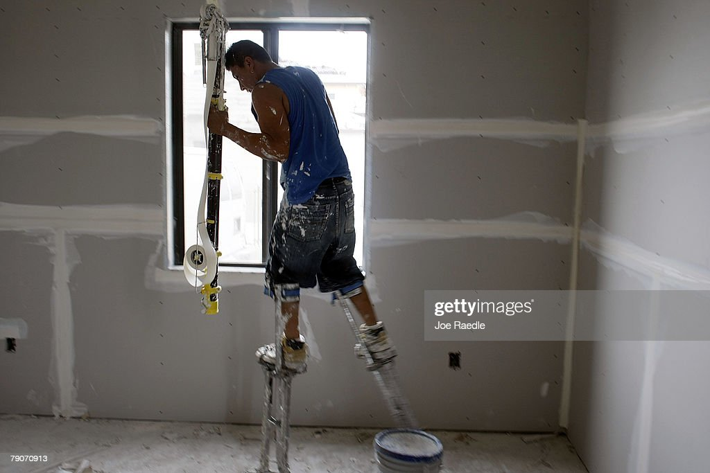A construction worker wears stilts as he paints a room in a house under construction January 17, 2008 in Miami, Florida. The Commerce Department released figures showing that new home construction is down 24.8 percent from 2006.