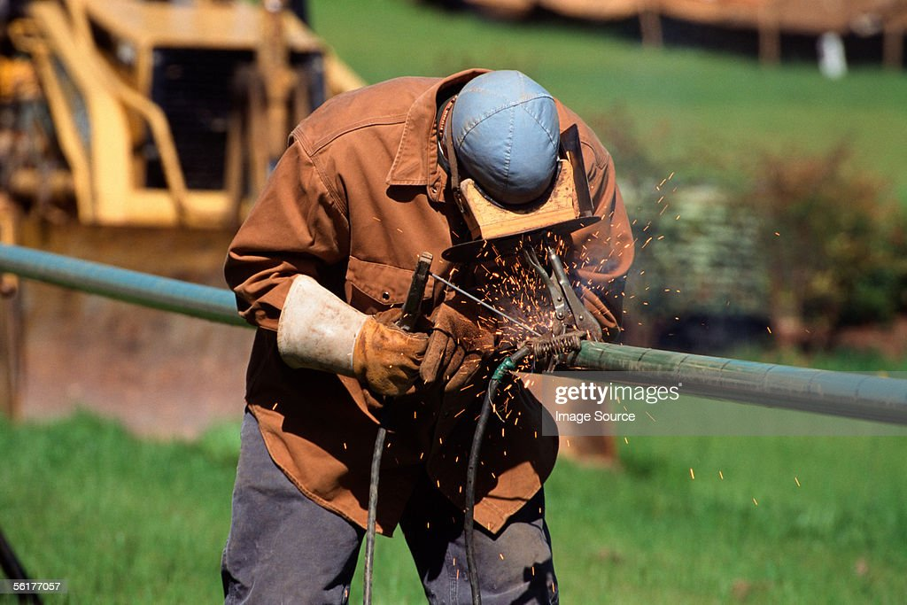 Construction worker welding a pipe : Stock Photo