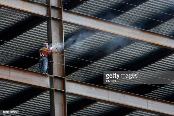 Construction Worker Welding Beam on High Rise Building